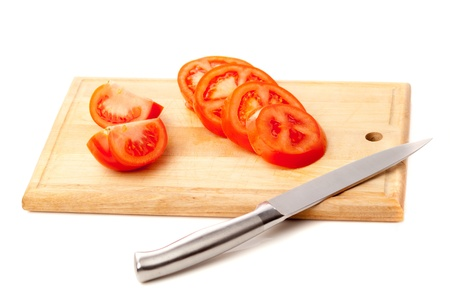 knife tomato: Picture of a sliced tomatoes on carving board on white background. Studio shot