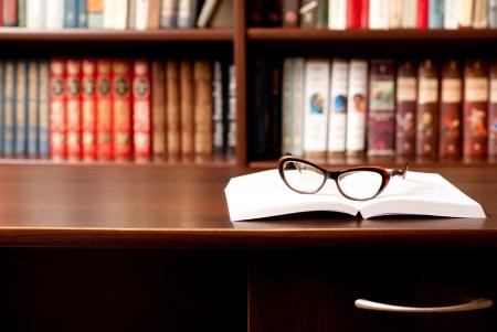 kütüphane: Açılmış kitap yatarken gözlük ve arka plan üzerinde birçok diğer kitaplar