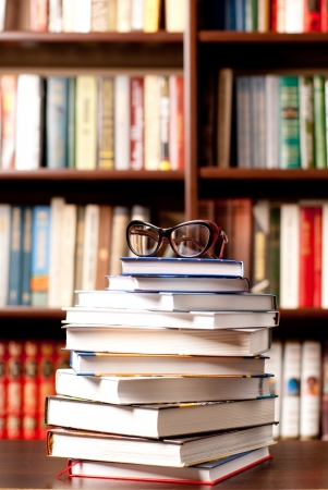 Eyeglasses lying on the opened book and many other books on background photo
