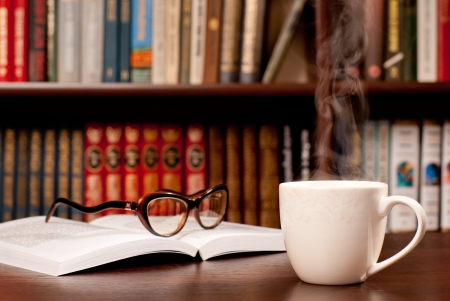 Eyeglasses lying on the opened book and a cup of tea