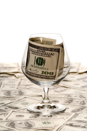 Picture of brandy glass filled with money. Studio shot Stock Photo