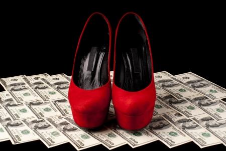 tacones rojos: Pares de zapatos femeninos rojos y d�lares sobre fondo negro Studio foto