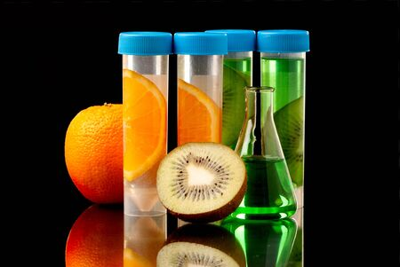 food research: Lb tubes filed with liquid of with fruits parts on black background.