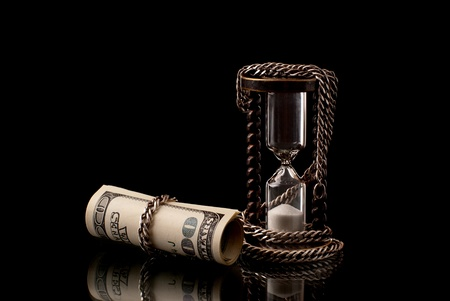 money metaphor: U.S>Dollars chained with hourglass with silver chaih. Black background. Studio shot. Stock Photo
