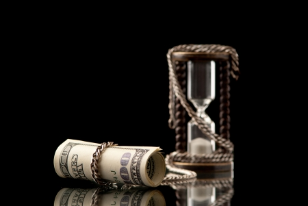 U.S>Dollars chained with hourglass with silver chaih. Black background. Studio shot. photo