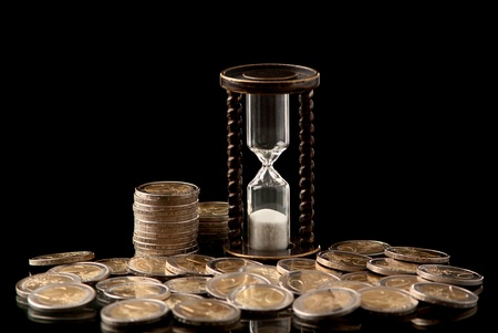 EURO coins and hourglass on black background. Studio shot. photo