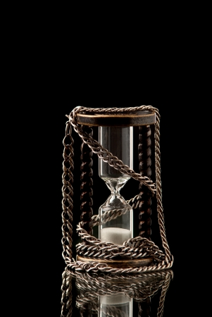 constrain: Hourlass with silver chain on black background. Studio shot.