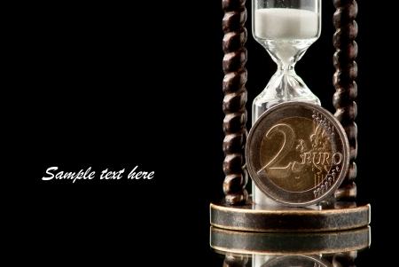 metall and glass: EURO coin and hourglass on black background. Studio shot.