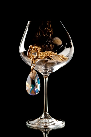 Jewellery and EURO coinbs in the broken wineglass. White background. Studio shot. photo