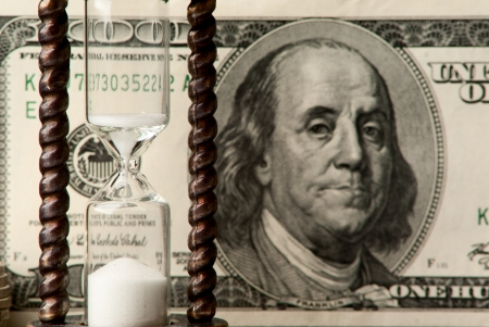 metall and glass: One hundred dollars note with hourglass. Studio shot.