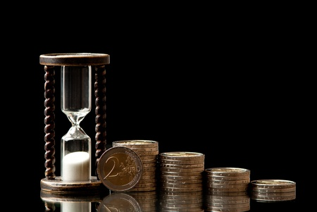 metall and glass: EURO coins and hourglass on black background. Studio shot.