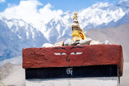 Picture of small buddhist Stupa with Eyes of Buddha on it, And snowy mountain peaks on background. Himalaya mountains, Nepal, Annapurna conservation area, Nepal. Stock Photo