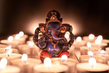 Souvenir statue of indiand god Ganesha among candles. Stock photo.