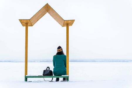 A young woman on a bench on the shore of a frozen lake. On the Edge of the World. Waiting for spring and summer. Loneliness concept. Meditative contemplation and inner reflection concept. Reklamní fotografie