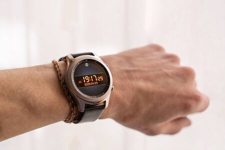 Male hand with electric watch showing precise time and date. Smart watch concept. Stock photo.