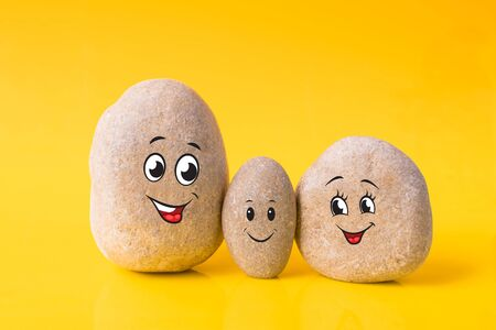 Group of stones with drawn funny faces on yellow background. Father, mother and son. Concept of happy family.