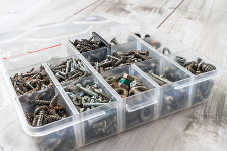Screws, bolts, nuts and other carpenter stuff in a plastic toolbox (hardware organizer). Stock photo.