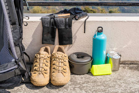 Trecking or hiking equipment - bagpack, boots, socks, folding knife, gas burner, water flask, kettle pot and flashlight. Outdoor activity concept. Still life close up stock photo.