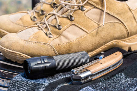 Trecking or hiking equipment - boots, socks, folding knife and flashlight. Stock photo Foto de archivo