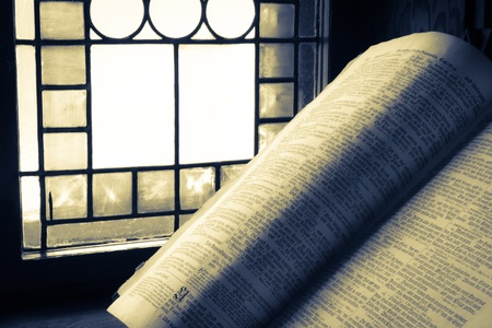 catholicism: Old Bible lit by stained glass