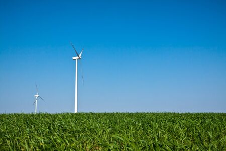 resourceful: Wind Turbines on green field with blue sky Stock Photo