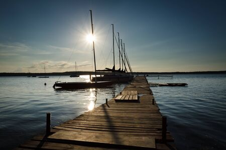 bridge over water: Sunset in wooden harbour at summer Stock Photo