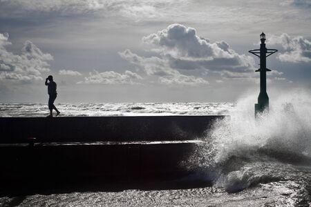 groyne: Tourist silhouette in groyne with big wave