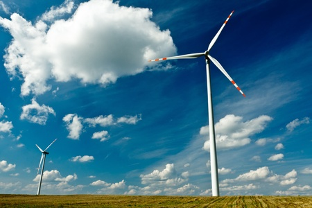 energy generation: Wind Turbines on gold field with blue sky