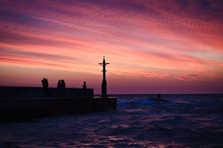 groyne: People on groyne with sunset