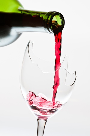 Red wine pouring to the broken glass photo