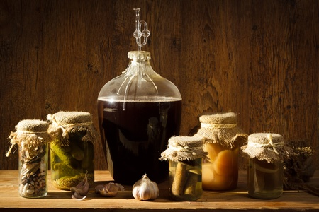 homemade style: Homemade wine in larder with vegetables jars