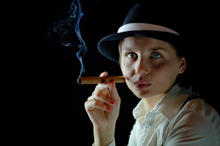 Woman in black hat with smoking cigar black  background isolated photo