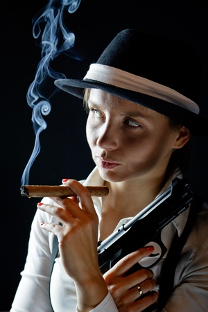 Woman in black hat with smoking cigar and gun black  background isolated photo