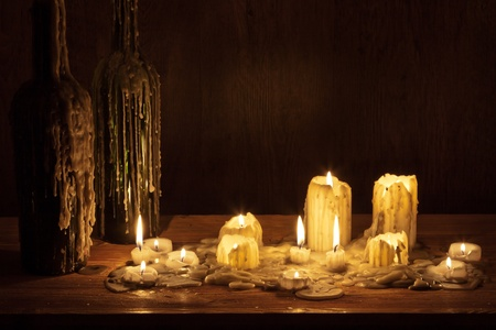 Melting candle in wooden shelf with bottle photo