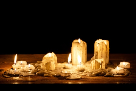Melting candle in wooden shelf photo