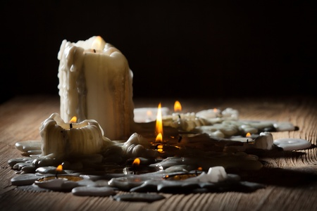 Melting candls with fire on wooden shelf photo
