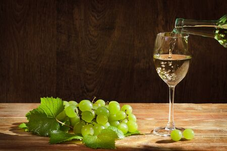 White wine pouring down to the glass with grapes photo