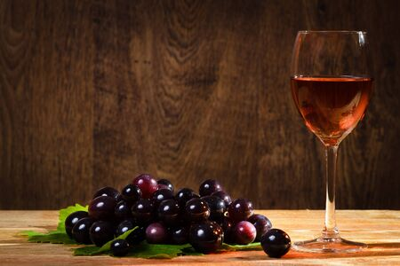 Glass of rose wine with dark grapes photo