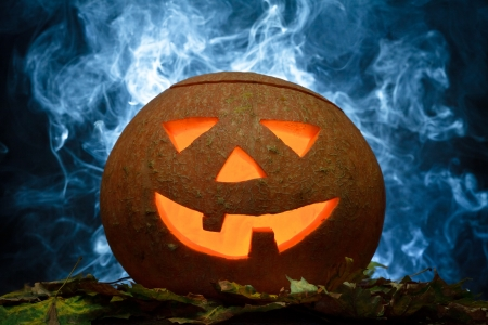 Halloween pumpkin on leafs with blue smoke Stock Photo