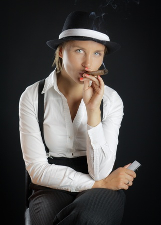 Woman in black hat with cigar in black background isolated photo