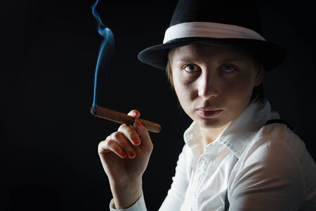 Woman in black hat with cigar in isolated photo
