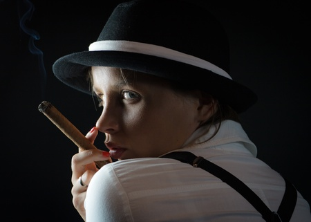 Woman in black hat with cigar in black isolated photo