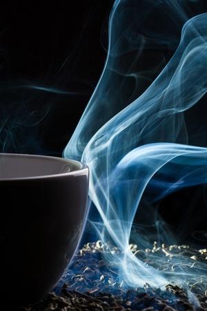 Tea and smoke on black background Stock Photo