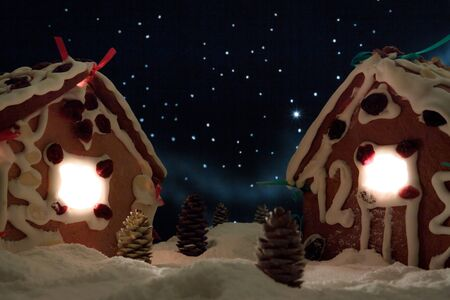 Snowy gingerbread cottage with stars in the background photo