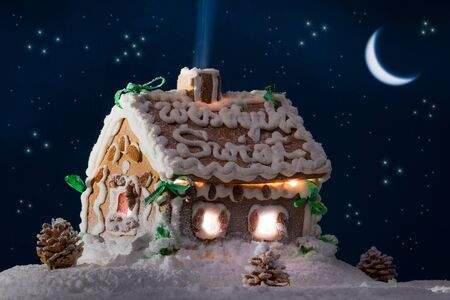 Snowy gingerbread cottage with stars and moon photo