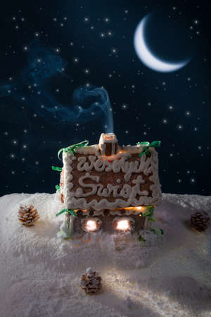 Snowy gingerbread cottage at night photo