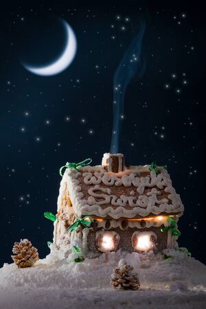 Blue smoke poured out of the gingerbread home at night in winter photo