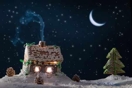 Snowy gingerbread cottage with stars at the lake photo