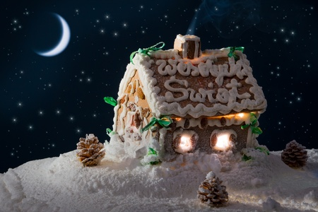 Snowy gingerbread home and moon at night in winter photo
