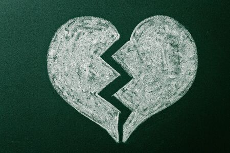 Broken heart on green blackboard photo